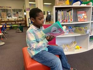 Boy reading a book sitting on a cushion in the Library Media Center